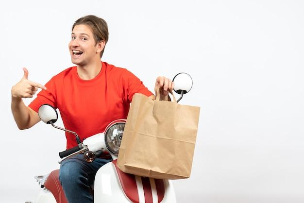 Joven sonriente feliz repartidor en uniforme rojo sentado en scooter sosteniendo una bolsa de papel en la pared blanca