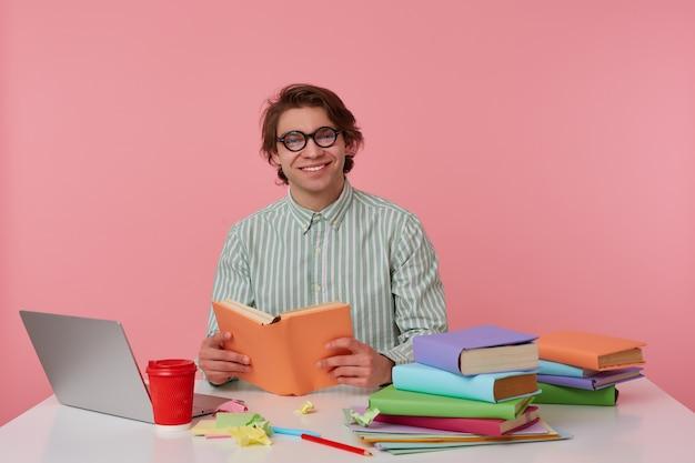 Joven sonriente con gafas viste camisa, se sienta junto a la mesa y trabaja con el cuaderno, se prepara para el examen, lee un libro, se ve alegre y disfruta de la lectura, aislado sobre fondo rosa.