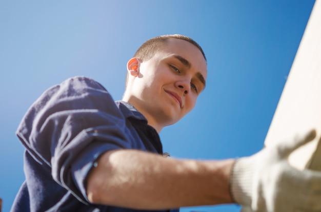 Un joven sonriente con guantes y ropa de trabajo está construyendo un techo.