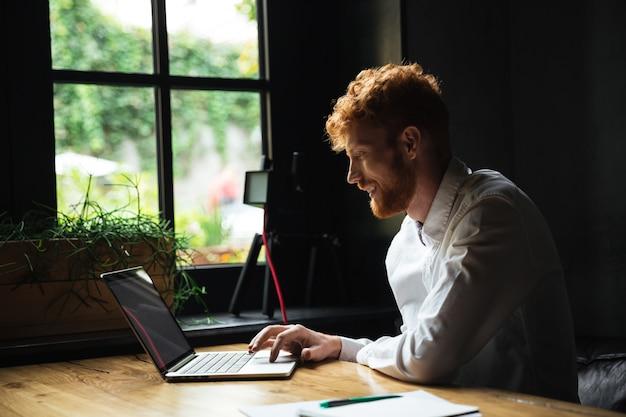 Joven sonriente guapo hombre barbudo con cabeza lectora en camisa blanca usando la computadora portátil en su lugar de trabajo