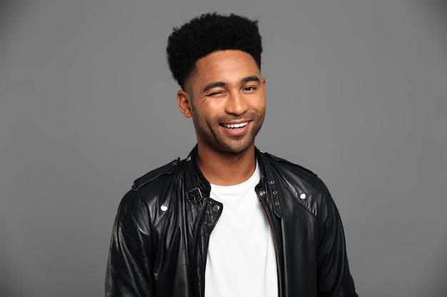Joven sonriente hombre africano en chaqueta de cuero negro guiña un ojo, mirando