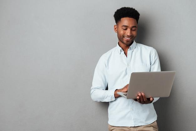 Joven sonriente hombre africano de pie y usando laptop