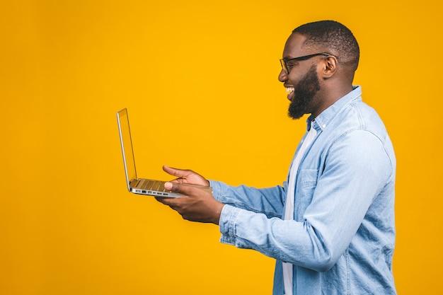 Joven sonriente hombre afroamericano de pie y usando la computadora portátil