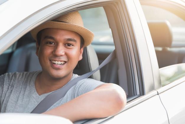 Joven sonriente hombre asiático sentado y conduciendo el coche