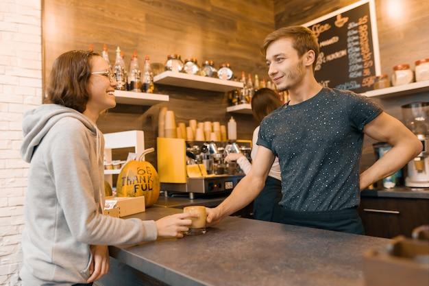 Joven sonriente hombre barista vendiendo bebidas a una niña adolescente en la cafetería.