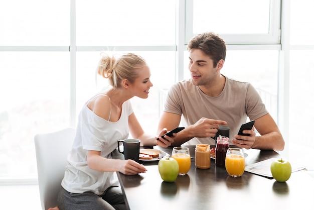Joven sonriente hombre y mujer hablando entre sí mientras desayuna