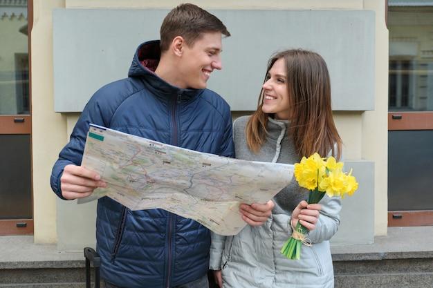 Joven sonriente hombre y mujer leyendo mapa