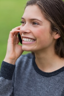 Joven sonriente llamada con su teléfono celular mientras está de pie