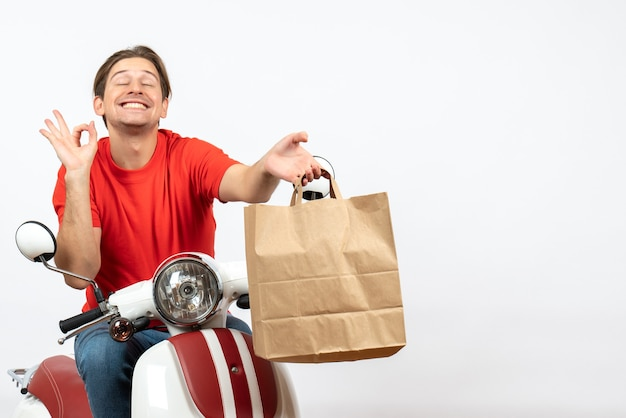 Joven sonriente mensajero emocional en uniforme rojo sentado en scooter dando bolsa de papel haciendo un gesto perfecto en la pared blanca