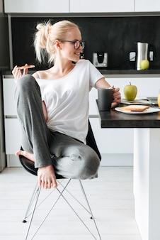 Joven sonriente mirando a un lado mientras desayuna en la cocina