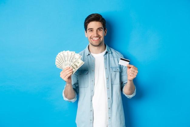 Joven sonriente mostrando dólares en efectivo y tarjeta de crédito, de pie sobre fondo azul.