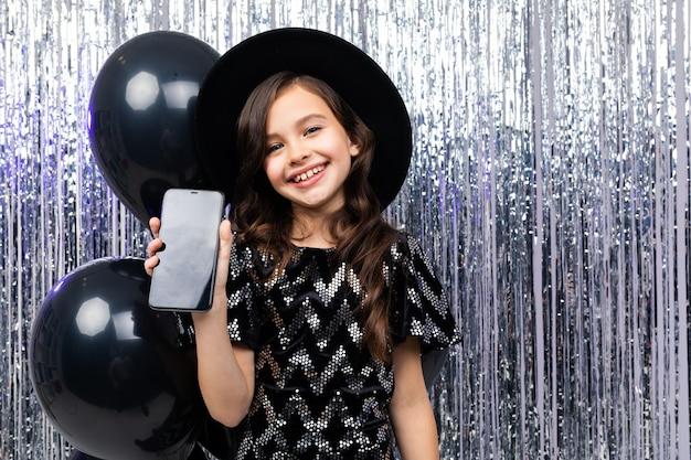 Joven sonriente muestra un protector de pantalla del teléfono con una maqueta en una fiesta en un brillante