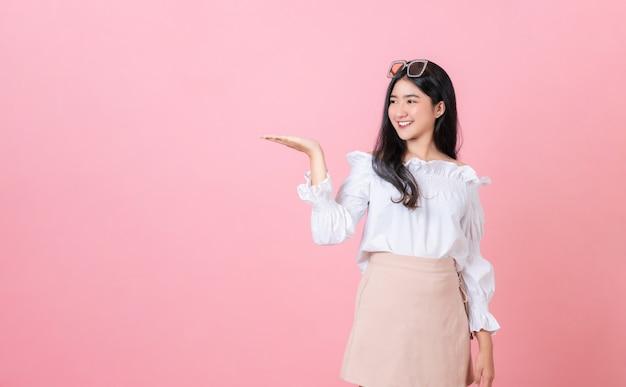 Joven sonriente mujer asiática de pie con las palmas abiertas y mirando para copiar espacio