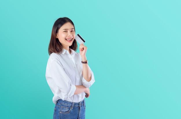 Joven sonriente mujer asiática con tarjeta de crédito en blanco con los brazos cruzados
