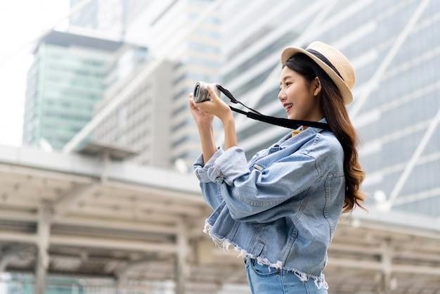 Joven sonriente mujer asiática tomando fotos con la cámara en la ciudad