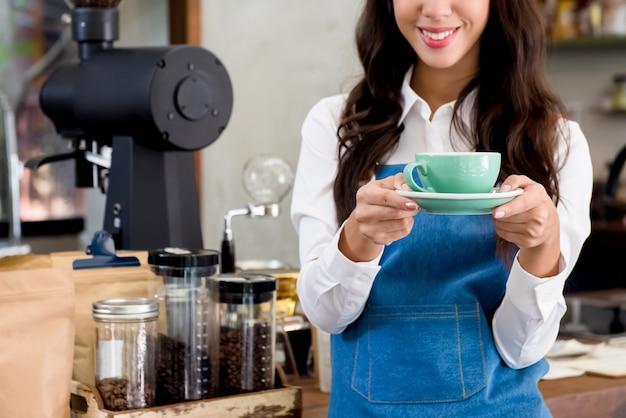 Joven sonriente mujer barista sirviendo una taza de café
