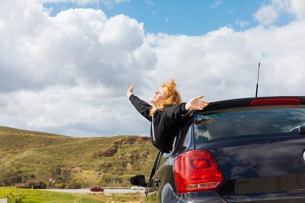 Joven sonriente mujer disfrutando de viaje