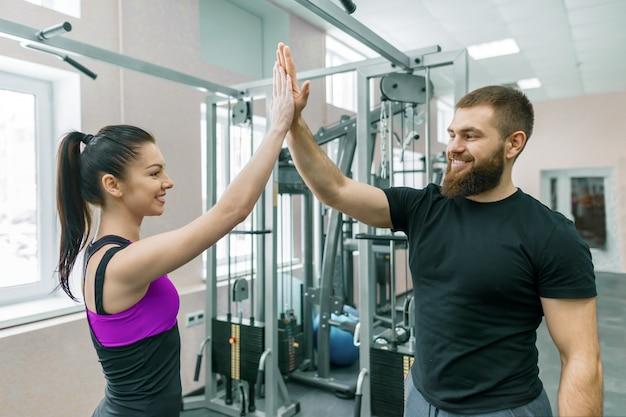 Joven sonriente mujer fitness dando choca esos cinco al entrenador personal.