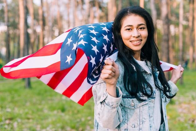 Joven sonriente mujer sosteniendo la bandera de estados unidos volando