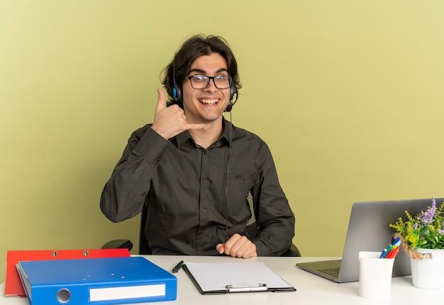 Joven sonriente oficinista hombre en auriculares con gafas ópticas se sienta en el escritorio con herramientas de oficina usando laptop gestos teléfono signo de mano aislado sobre fondo verde con espacio de copia