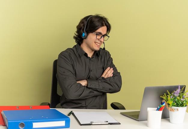 Joven sonriente oficinista hombre en auriculares con gafas ópticas se sienta en el escritorio con herramientas de oficina usando y mirando portátil con los brazos cruzados aislado sobre fondo verde con espacio de copia