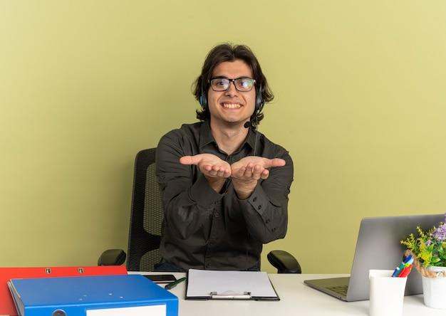 Joven sonriente oficinista hombre con gafas ópticas se sienta en el escritorio con herramientas de oficina usando laptop y mantiene las manos abiertas mirando a cámara aislada sobre fondo verde con espacio de copia