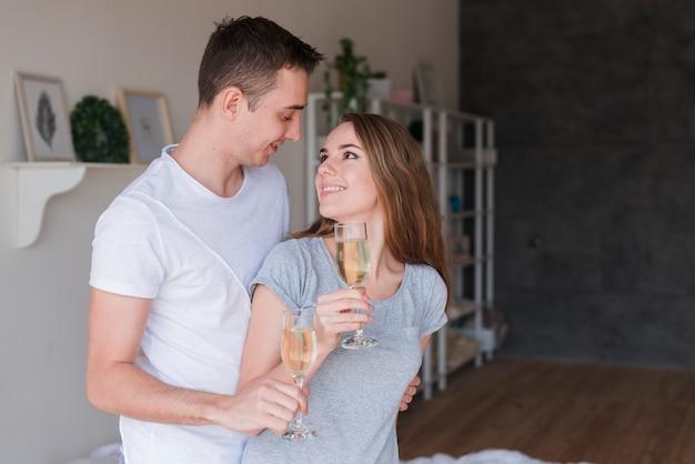 Joven sonriente pareja abrazándose con gafas en casa