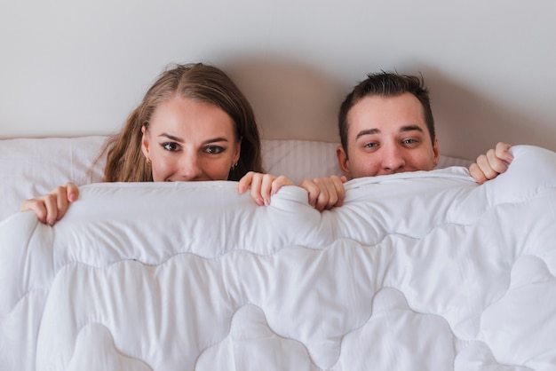 Joven sonriente pareja acostada en la cama y mirando fuera de edredón