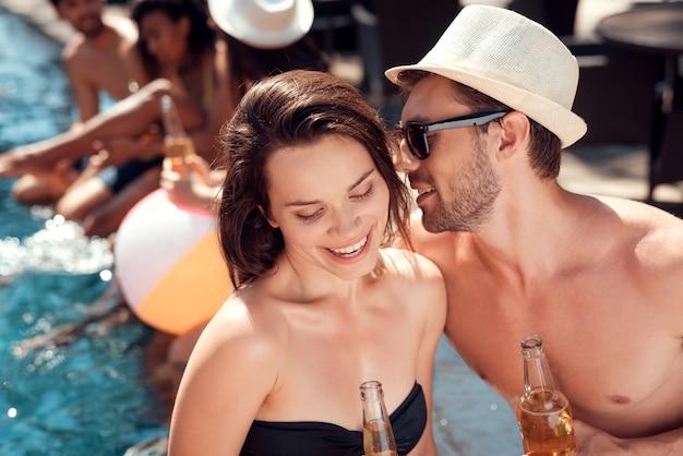 Joven sonriente pareja bebiendo vino en la piscina