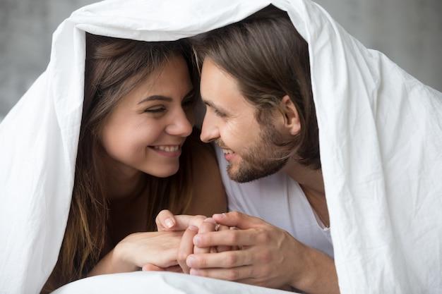 Joven sonriente pareja en la cama divirtiéndose cubierto con manta