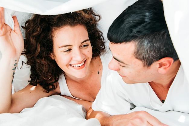 Joven sonriente pareja cubierta por edredón