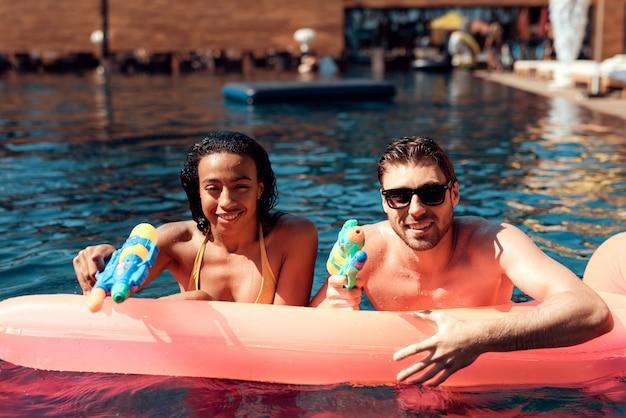 Joven sonriente pareja divirtiéndose en la piscina