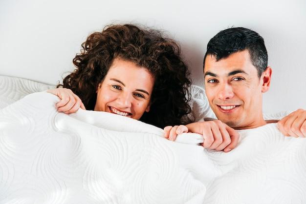 Joven sonriente pareja bajo edredón