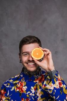 Un joven sonriente con piercing en los oídos y la nariz sosteniendo una rodaja de naranja frente a sus ojos contra un fondo gris