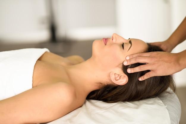 Joven sonriente, recibiendo un masaje de cabeza en un centro de spa.