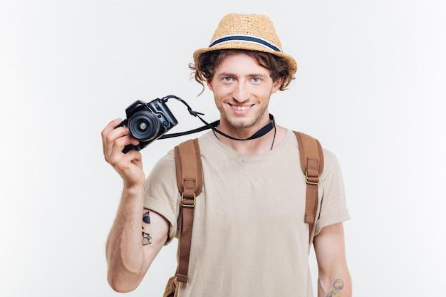 Joven sonriente sosteniendo una cámara retro aislado sobre un fondo blanco.