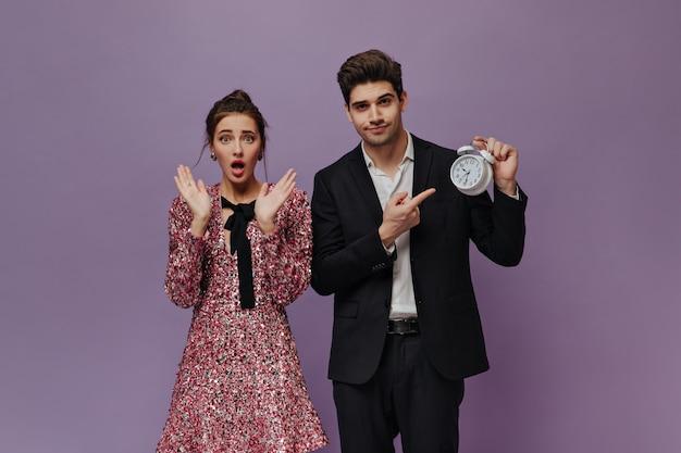 Joven sorprendida con cabello morena posando en mini vestido rosa cerca de un niño bonito con traje negro y mostrando la hora en el reloj