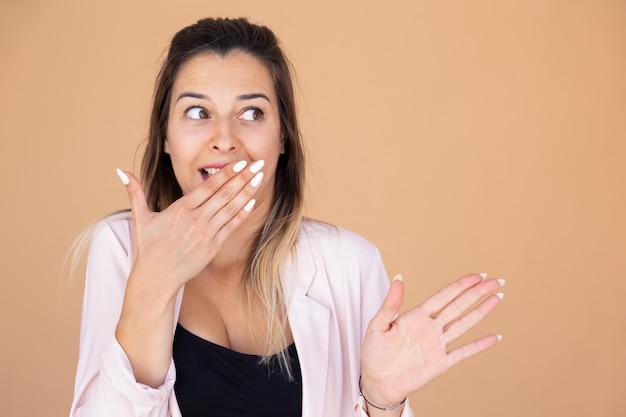 Joven sorprendida cubriendo la boca con la mano