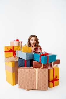 Joven sorprendida mujer rizada entre cajas de regalo