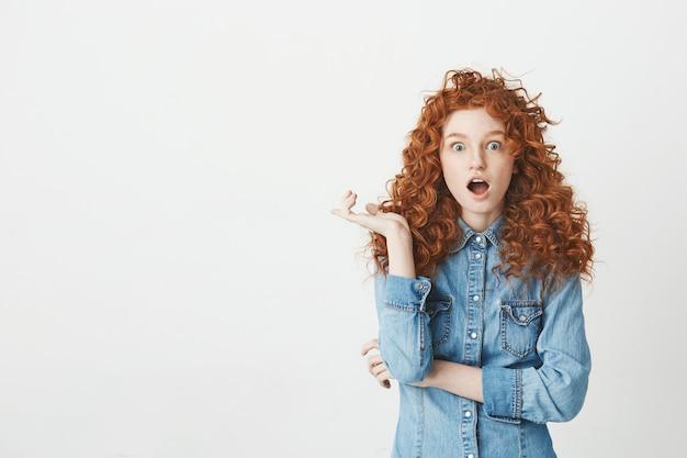 Joven sorprendida con el pelo rojo rizado con los ojos abiertos. copia espacio