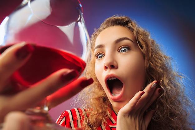 La joven sorprendida en ropa de fiesta posando con copa de vino