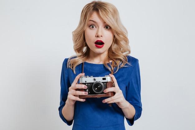 Joven sorprendida sosteniendo la cámara sobre la pared blanca