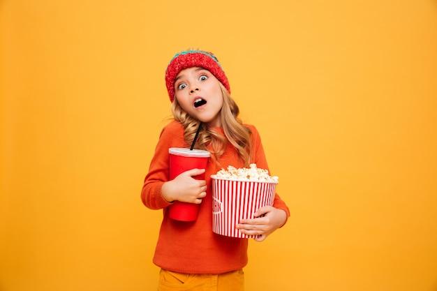 Joven sorprendida en suéter y sombrero con palomitas de maíz y vaso de plástico mientras mira a la cámara sobre naranja