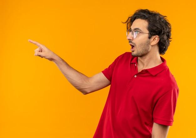 Joven sorprendido en camisa roja con gafas ópticas se encuentra de lado y apunta al lado aislado en la pared naranja