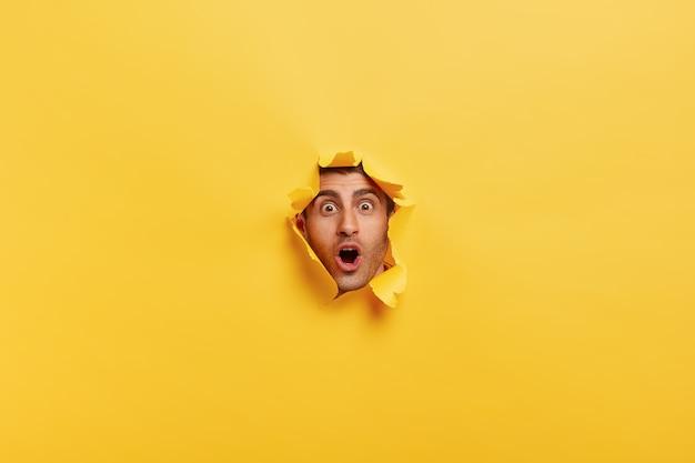 Joven sorprendido con cerdas mantiene la boca bien abierta, mira a través de la pared de papel rasgada