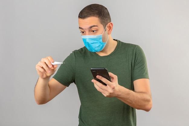 Joven sorprendido en máscara médica mirando el termómetro digital y sosteniendo un teléfono inteligente en la mano aislado en blanco