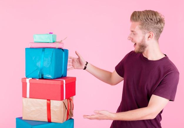 Joven sorprendido mirando la pila de cajas de regalo sobre fondo rosa