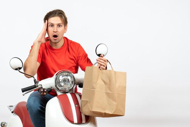 Joven sorprendido repartidor en uniforme rojo sentado en scooter sosteniendo una bolsa de papel posando para el frente en la pared blanca