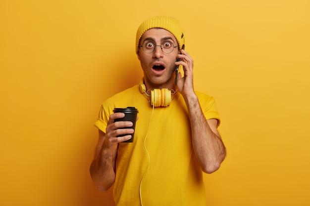 Un joven sorprendido tiene una conversación telefónica, jadea nerviosamente, mira con pánico, usa una camiseta informal, un sombrero y gafas