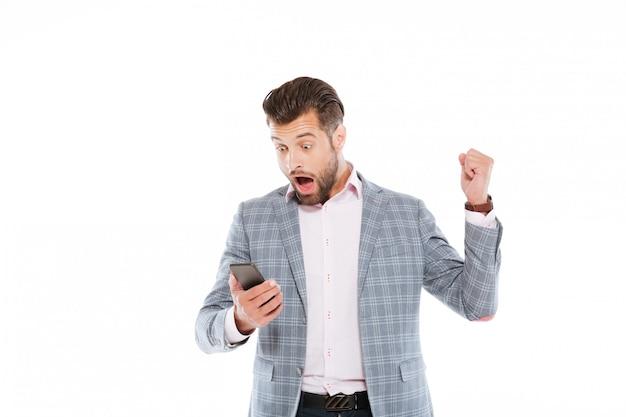 Joven sorprendido usando teléfono móvil.